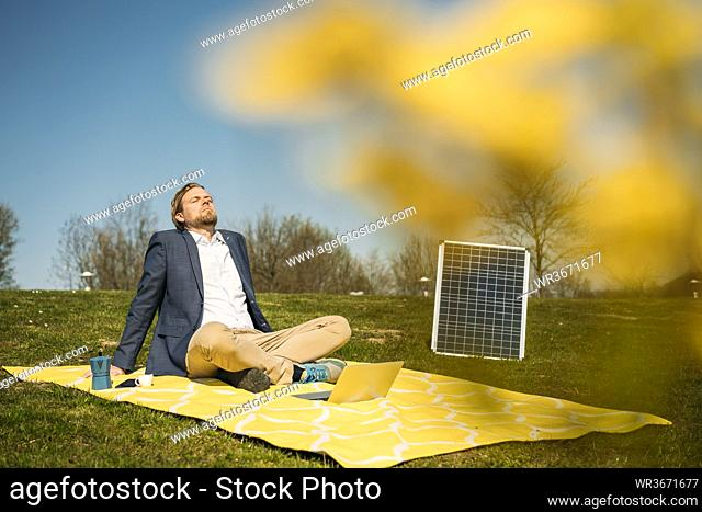 Male professional relaxing on picnic blanket by solar panel at park during sunny day