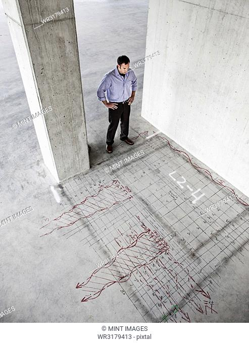 Caucasian businessman standing in a new raw office space looking at an office layout sketched onto the floor of the space