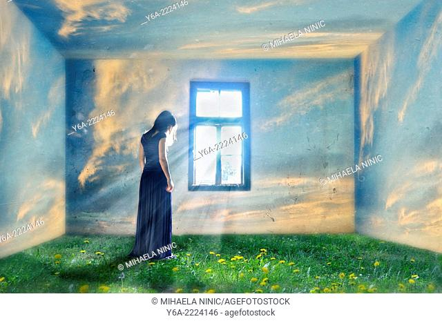 Composite image of a woman standing by the window and grass and clouds