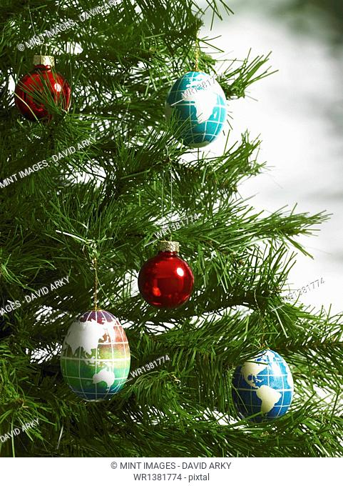 Still life. Green leaf foliage and decorations. A pine tree branch with green needles. Christmas decorations. A small group of red and blue tree ornaments