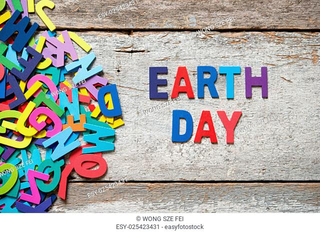 "The colorful words """"EARTH DAY"""" made with wooden letters next to a pile of other letters over old wooden board"