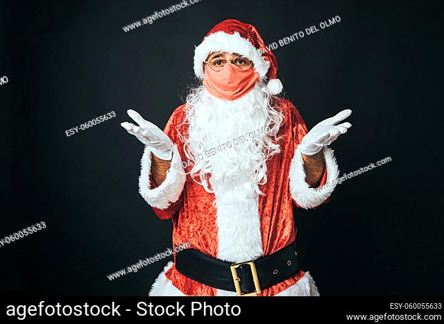 Man dressed as Santa Claus wearing a red mask and disgruntled gesture, on black background. Christmas concept, Santa Claus, gifts, celebration