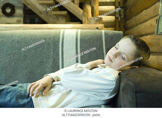 Preteen boy falling asleep on couch