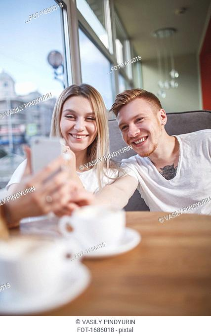 Happy young couple taking selfie with mobile phone while sitting at restaurant