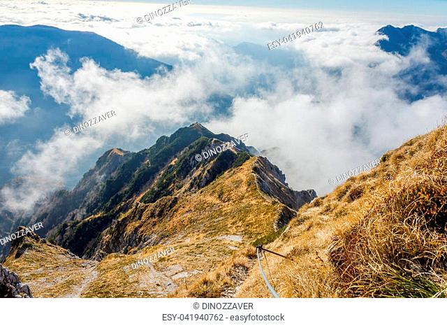 Via ferrata over the sea of clouds to bivouac Dino above Udine. The Alps, Italy