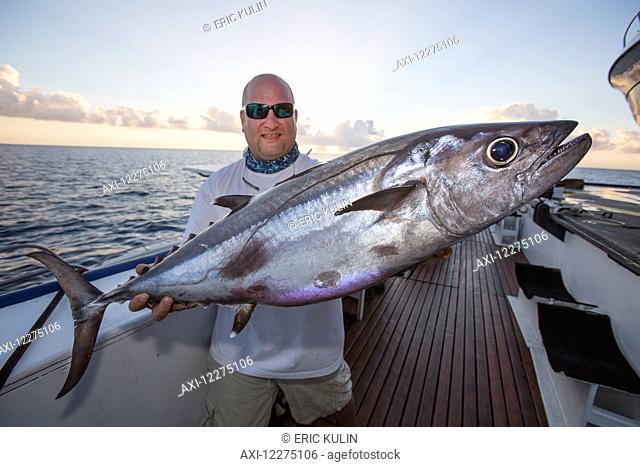 A fisherman poses with a dogtooth tuna (Gymnosarda unicolor); Tahiti