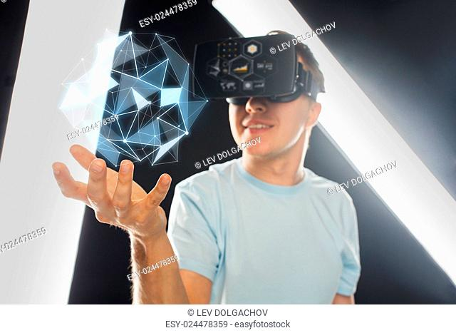 3d technology, virtual reality, science and people concept - close up of happy young man with virtual reality headset or 3d glasses playing game and holding...