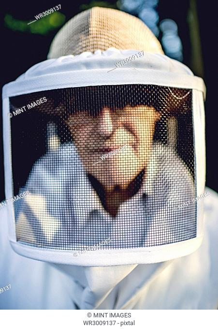 Close up of beekeeper looking into shot wearing a veil