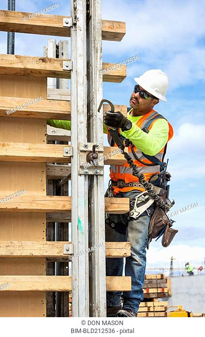 Hispanic worker holding hook at construction site