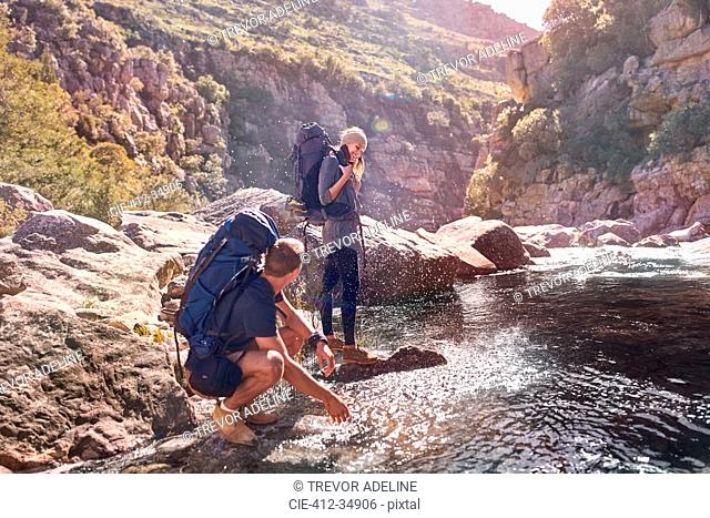 Young couple with backpacks hiking, splashing water at stream