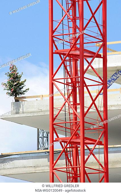 Red crane with topping-out tree at a construction site