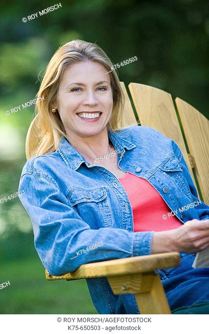 smililng woman sitting in chair outdoors