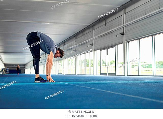 Runner stretching on indoor running track