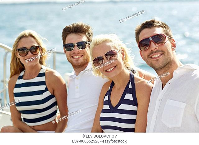 vacation, travel, sea, friendship and people concept - smiling friends sitting and talking on yacht deck