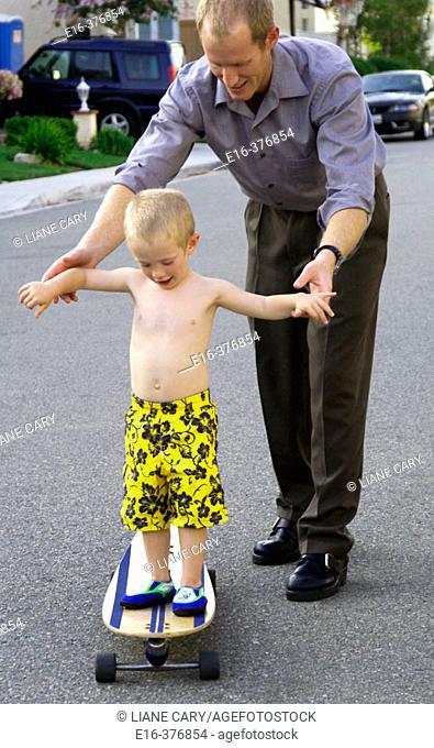 father teaching son balance on skateboard