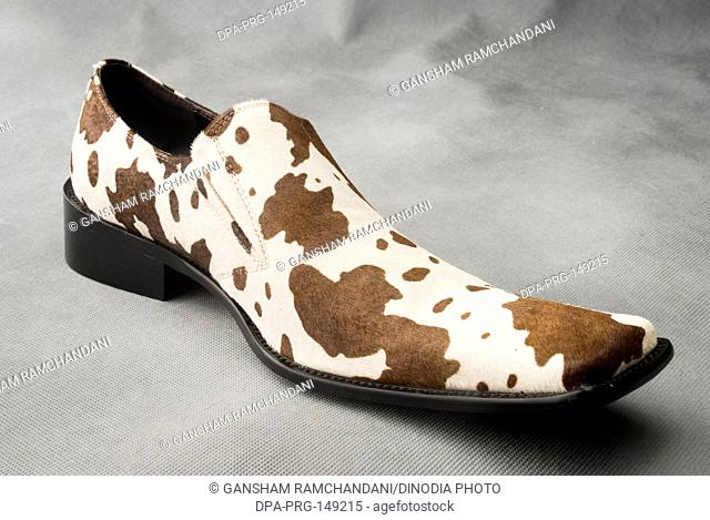 Skin color leather shoe with patches on gray background MR