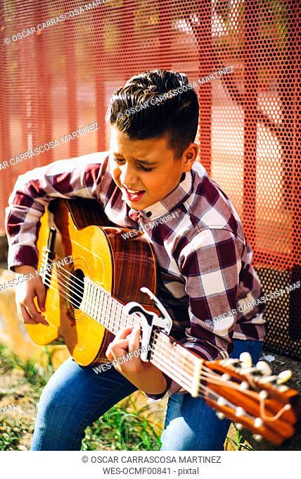 Gypsy boy playing guitar outdoors