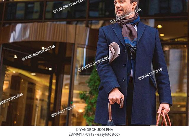 Successful businessman is standing near office and waiting. He is carrying newspaper and smiling. Man is holding umbrella and bag