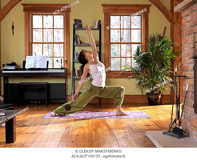 Young woman practicing yoga indoors in a living room on a bright sunny day