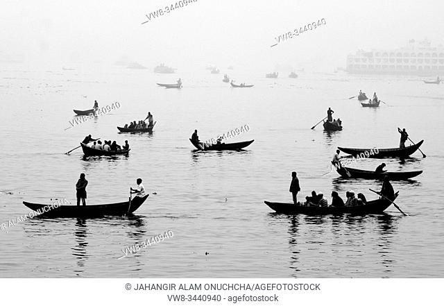 "Bangladesh â. "" January 06, 2014: In the midday afternoon, people are crossing the river by boat and this year the fog of the winter is engulfed in the river..."