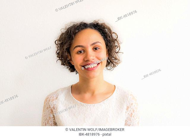 Portrait of a young smiling woman against a white background, Germany