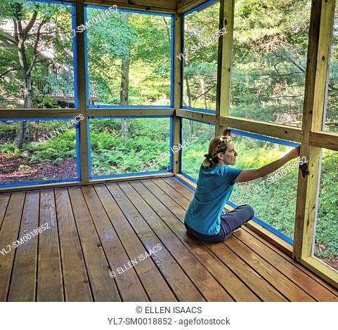 Woman putting blue tape along screens in preparation for painting the posts of a screened porch in a DIY home improvement project