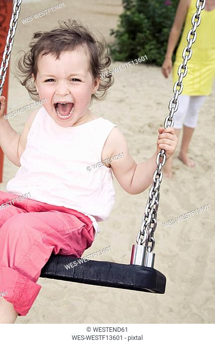 Germany, Berlin, Girl 3-4 at playground, sitting on swing, laughing, portrait, close-up