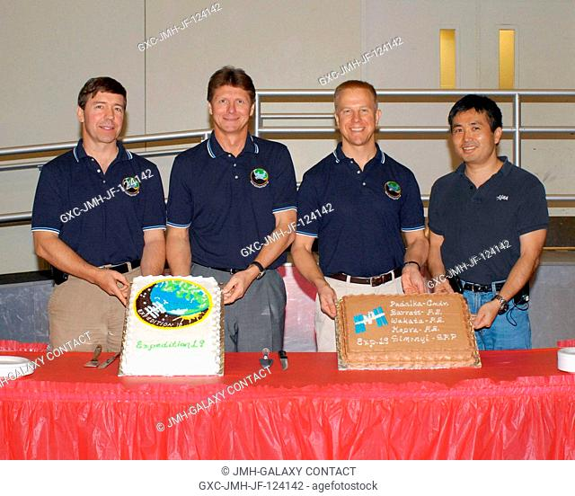 Expedition 19 crewmembers celebrate the end of formal crew training with a cake-cutting ceremony in the Jake Garn Simulation and Training Facility at NASA's...