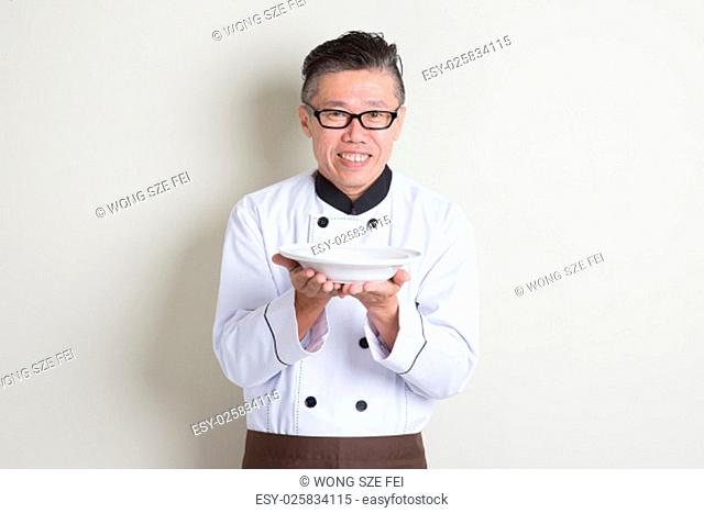 Portrait of 50s mature Asian male chef in uniform presenting dish, empty plate ready for food, standing on plain background with shadow, copy space