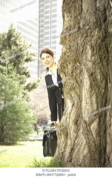 Hispanic businesswoman peeking around tree