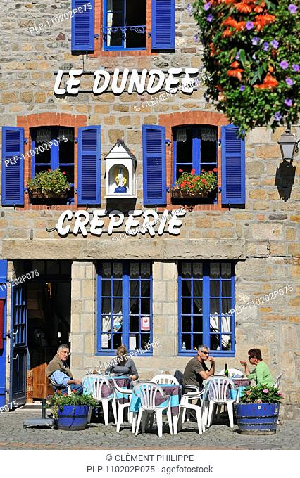 Tourists on terrace eating crepes at crêperie in Paimpol, Côtes-d'Armor, Brittany, France