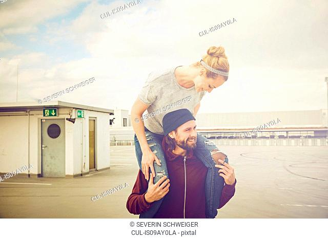 Mid adult woman getting shoulder ride from boyfriend on rooftop parking lot