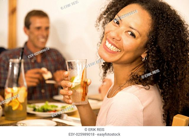 Happy Afro-American woman at the restaurant having a drink