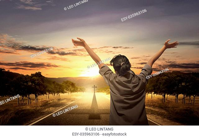 Back view of woman raising hand with open palm while praying over sunset background