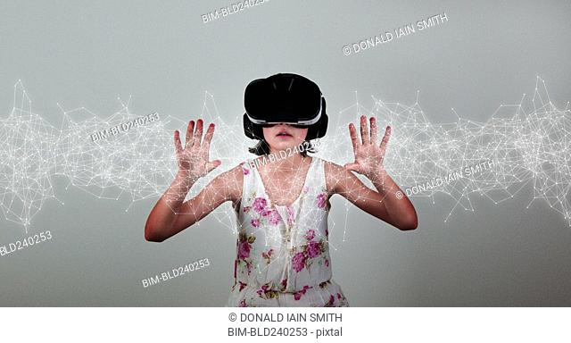 Mixed Race girl wearing virtual reality goggles