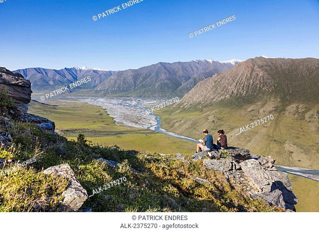Hikers sit on rock outcrop and view the confluence of the Canning River and the Marsh Fork of the Canning river in the Arctic National Wildlife Refuge