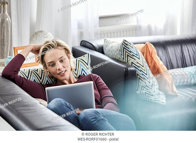 Young woman with tablet lying on couch at home