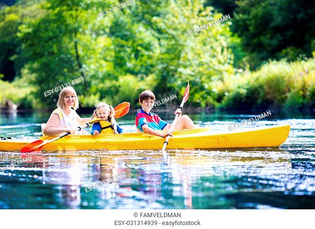 Happy family with two kids enjoying kayak ride on beautiful river. Mother with little girl and teenager boy kayaking on hot summer day