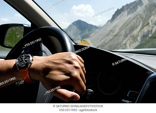 Man hand holding on to the steering wheel of a car
