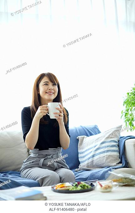 Young Japanese woman having breakfast at home