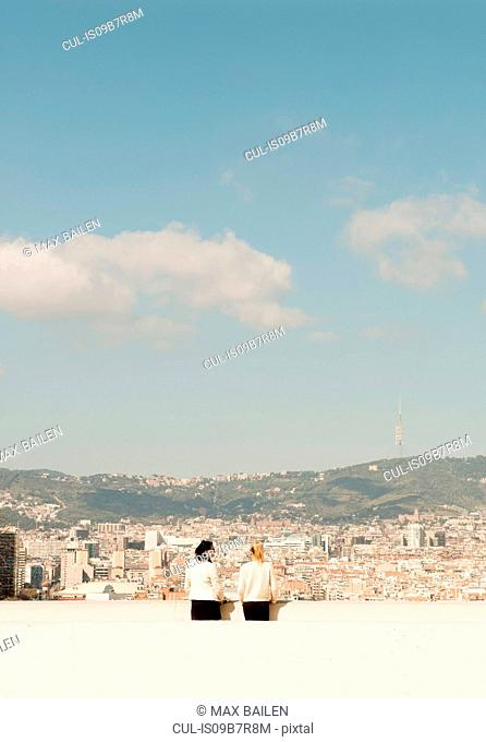 Rear view of female tourists looking out over cityscape, Barcelona, Spain