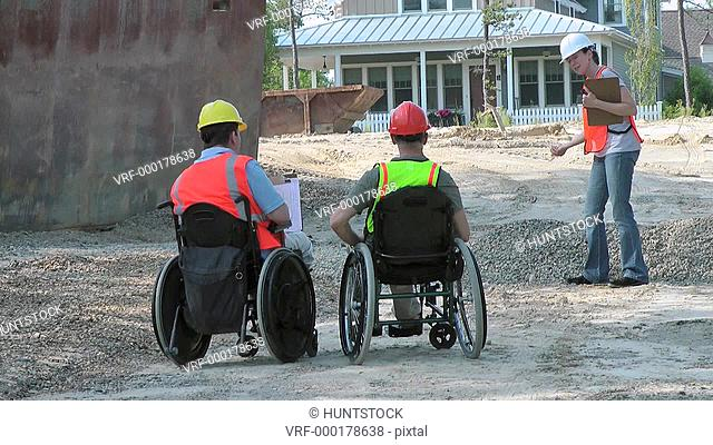 Construction engineers discussing site issues, men in wheelchairs with spinal cord injuries