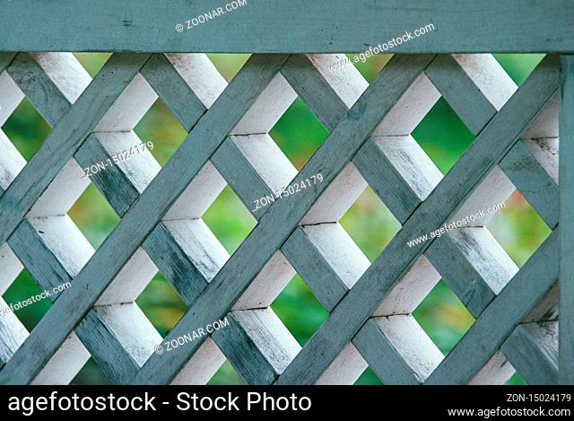 diamond-shaped wooden lattice painted white against the background of a green lawn