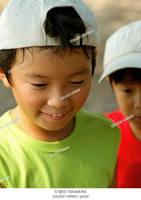 Close-up of a boy looking down with a boy in the background