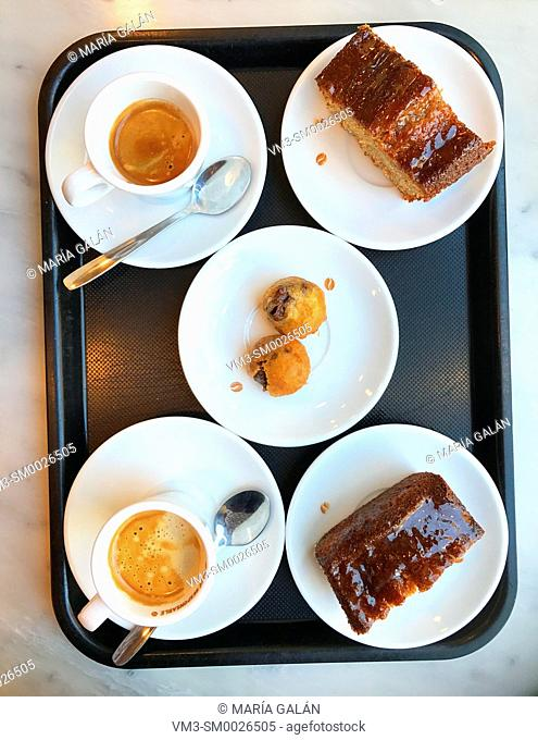 Two cups of coffees and cakes on a tray. View from above