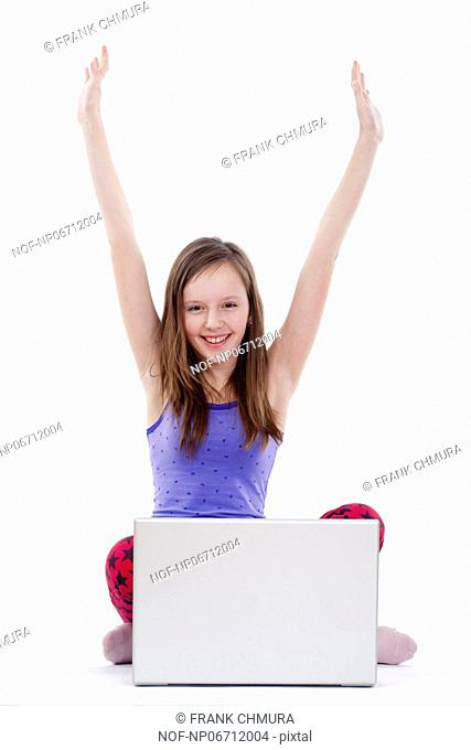young girl sitting in front of her laptop cheering - isolated on white