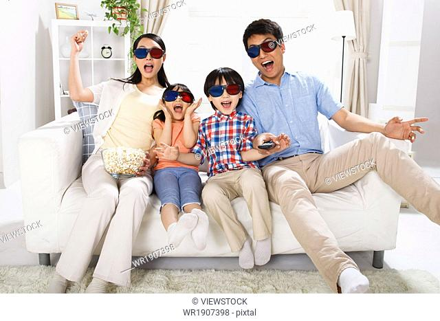 A family of four with 3D glasses in the living room