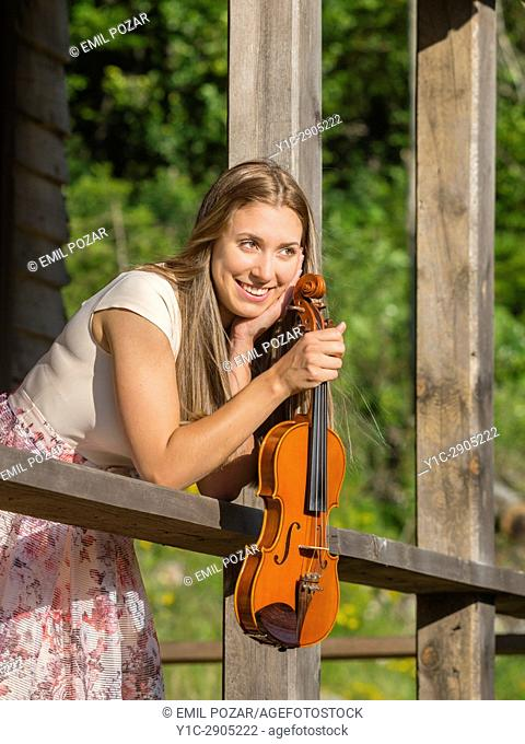 Violin player violinist outdoors inclined on wooden fence smiling away