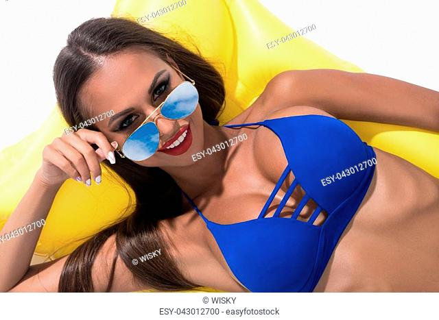 Sexy tanned brunette in nice blue bicini and color sunglasses smiling and enjoying her summer weekend sunny shot