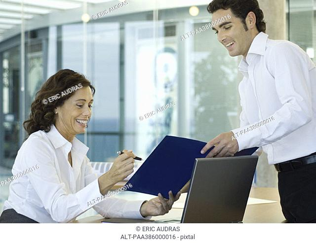 Male office worker showing file to businesswoman